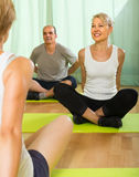 Mature couple practicing yoga with instructor Royalty Free Stock Image