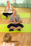 Mature couple practicing yoga with instructor Stock Photo