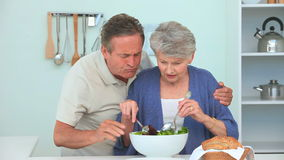Mature couple preparing a salad stock video footage
