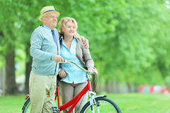Mature couple pushing a bicycle in park Stock Images
