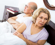Mature couple quarrels in bed Stock Photography