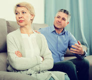 Mature couple quarrels. Mature husband and wife quarrels with each other at clarification of the family relation in home royalty free stock photo