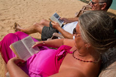 Mature couple reading. Mature couple relaxing, sitting in sun chairs on the beach reading Royalty Free Stock Photography