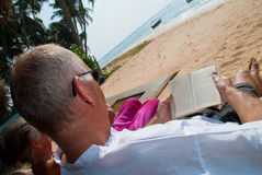 Mature couple reading. Mature couple relaxing, sitting in sun chairs on the beach reading Stock Images