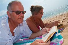 Mature couple reading on beach. Mature couple reading, relaxing on tropical beach. The sky is blue with clouds in the background Stock Photos