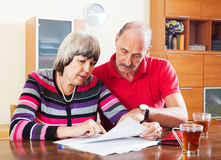 Mature couple reading financial document Royalty Free Stock Photo