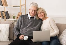 Mature couple reading news on laptop and drinking coffee stock images