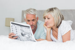 Mature couple reading newspaper in bed Stock Photo