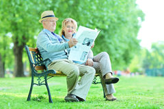 Mature couple reading a newspaper in park. Happy mature couple reading a newspaper outdoors Royalty Free Stock Photo