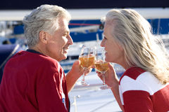 Mature couple, in red jumper and t-shirt, sitting on deck of yacht moored at harbour jetty, making celebratory toast with wine gla Stock Photos