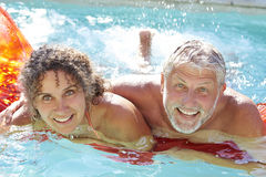Mature Couple Relaxing On Airbed In Swimming Pool stock image