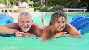 Mature Couple Relaxing On Airbed In Swimming Pool. Slow motion sequence of mature couple lying on airbed in swimming pool and swimming towards camera.Shot on stock footage
