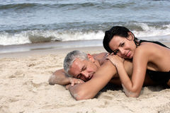 Mature couple relaxing on the beach. Attractive mature couple relaxing on the beach Royalty Free Stock Photo