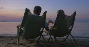 Mature couple relaxing on the beach and drinking cocktails stock video footage