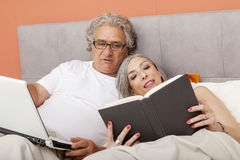 Mature couple relaxing in bed reading Royalty Free Stock Image