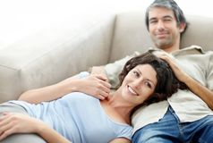 Mature couple relaxing on couch and smiling Stock Photos