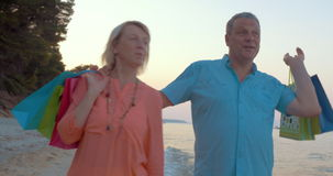 Mature couple relaxing with seaside walk after shopping stock footage