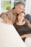 Mature couple relaxing on sofa. Stock Image