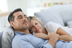 Mature couple relaxing on sofa Royalty Free Stock Photos