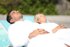 Mature couple relaxing by swimming pool Royalty Free Stock Images