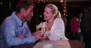 Mature Couple Relaxing Together At Rooftop Bar. Mature couple enjoying drinks and talking at rooftop bar - they make a toast together.Shot in 4k on Sony FS700 at stock video footage