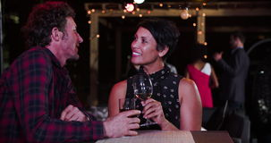 Mature Couple Relaxing Together At Rooftop Bar. Mature couple enjoying drinks and talking at rooftop bar together.Shot in 4k on Sony FS700 at frame rate of 25fps stock video