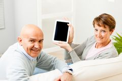 Mature couple displaying a blank tablet-pc Royalty Free Stock Images