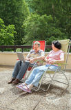 The mature couple rest on big balcony in summer time Royalty Free Stock Image