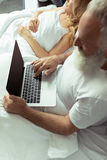 Mature couple resting in bed, man using laptop Stock Photo