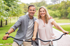 Mature couple riding bicycle. Mature couple riding bikes at park in a summer day. Portrait of smiling senior couple enjoying the ride on bicycle in park stock photo
