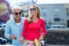 Mature couple riding bicycle on city street Stock Photos
