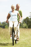 Mature couple riding bike in countryside Royalty Free Stock Photo