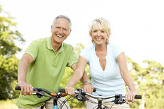 Mature couple riding bikes Royalty Free Stock Photography