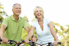 Mature couple riding bikes royalty free stock photos