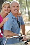 Mature couple riding bikes Stock Image