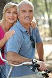 Mature couple riding bikes Stock Image