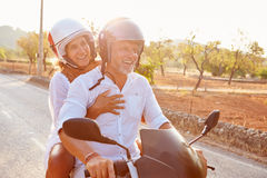 Mature Couple Riding Motor Scooter Along Country Road Royalty Free Stock Photography