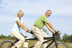 Mature couple riding tandem Royalty Free Stock Photo