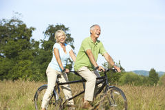 Mature couple riding tandem Stock Photo