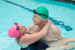 Mature couple romancing in swimming pool Royalty Free Stock Image