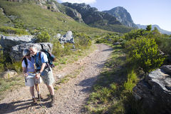 Mature couple, with rucksacks, hiking on mountain trail, looking at map, man leaning on hiking pole. Mature couple, with rucksacks, hiking on mountain trail stock image