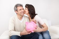 Mature couple saving money in piggybank. At home Royalty Free Stock Image