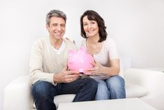 Mature couple saving money in piggybank. At home Stock Images