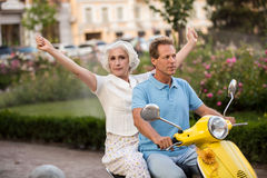 Mature couple on a scooter. Woman with raised hands. Go on a trip together. Feeling of freedom Royalty Free Stock Image