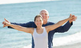 Mature couple at sea beach. Happy mature couple standing together at sea beach Stock Photo
