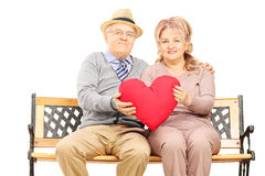 Mature couple seated on bench holding a big red heart Royalty Free Stock Photography