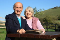 Mature couple seated in countryside setting. Stock Photography
