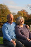 Mature couple seated on a park bench. Royalty Free Stock Photography