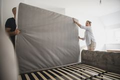 Couple Setting Up Bed Together in New Home Royalty Free Stock Photography