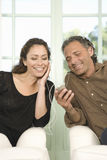 Mature couple sharing headphones. Mature couple sharing earphones while listening to music with an mp4 in their home's living room Royalty Free Stock Images